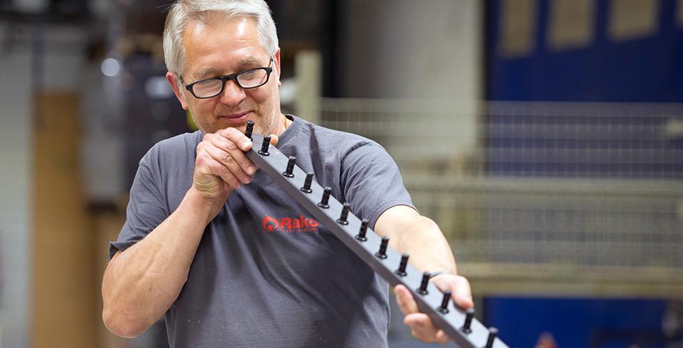 Rako Mitarbeiter prüft ein Bauteil für Fiberglaslattenroste